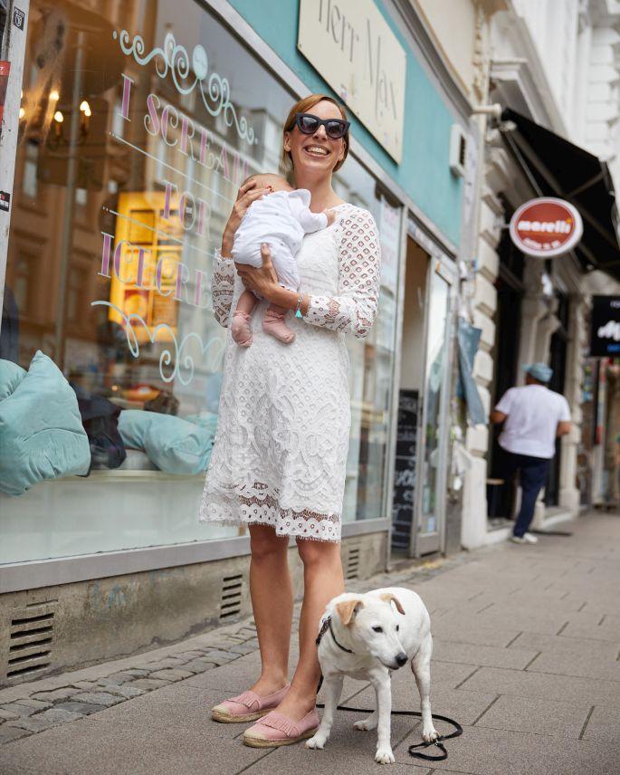 Frau mit Baby und Hund im weißen Spitzenkleid und Espadrilles