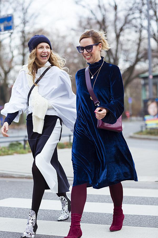 Zwei Frauen gehen lachend auf der Straße und tragen mögliche Outfits für die Berlin Fashion Week