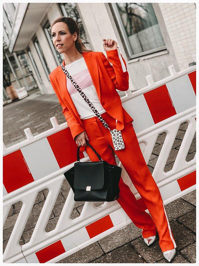 Frau im roten Hosenanzug vor einer Baustelle während der Fashion Week Berlin