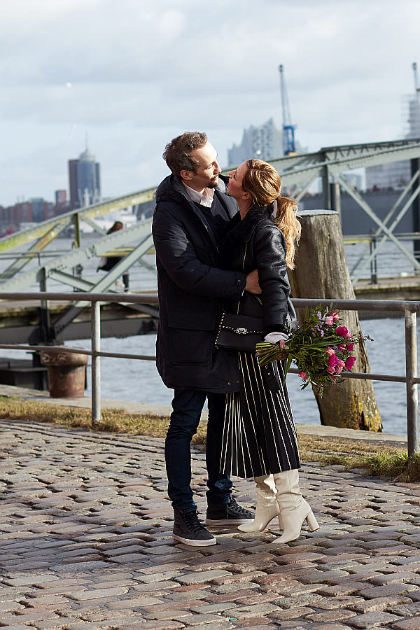Mann und Frau zeigen die Mode der halblangen Röcke am Hafen