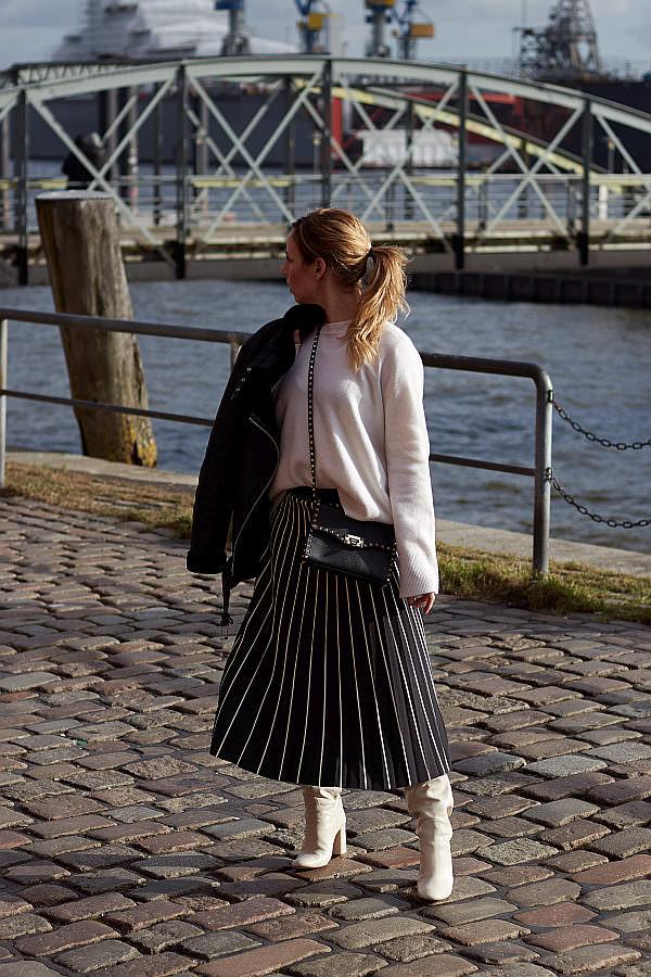 Frau kombiniert zu der Mode der halblangen Röcke weiße Stiefel und einen Kaschmir-Pullover