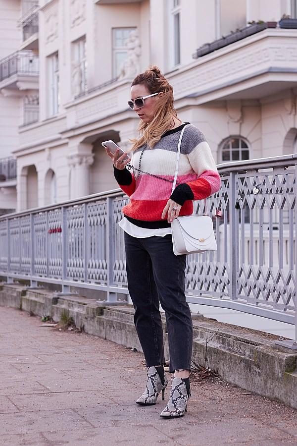 Valentinstagsgrüsse von Frau am Geländer mit Blockstreifenpullover und Wandler Tasche