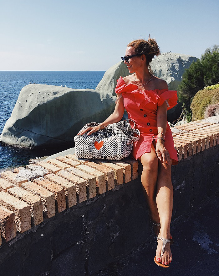 Ischia Sehenswürdigkeiten Frau im roten Kleid mit Blick auf die Scogli degli Innamorati