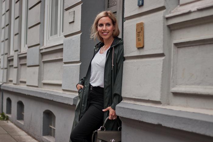 Frau im Outdoor Outfit zeigt wie man den Regenmantel kombinieren kann