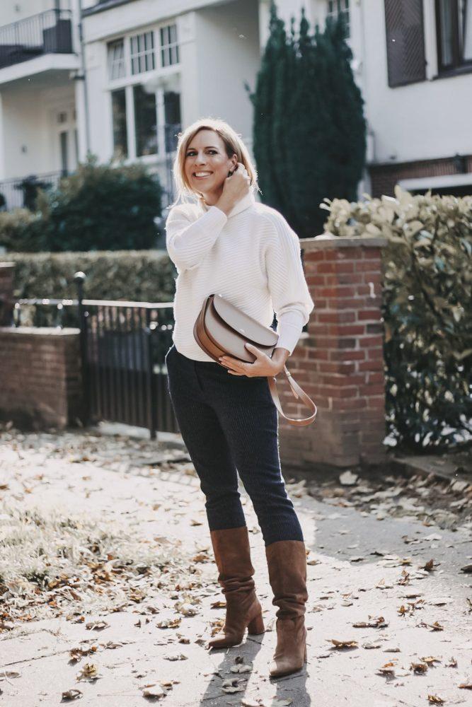 Peter Hahn online Outfit cremefarbener Cashmere Pullover kombiniert mit marineblauer Stoffhose und Cross Body Bag von A.P.C. Paris
