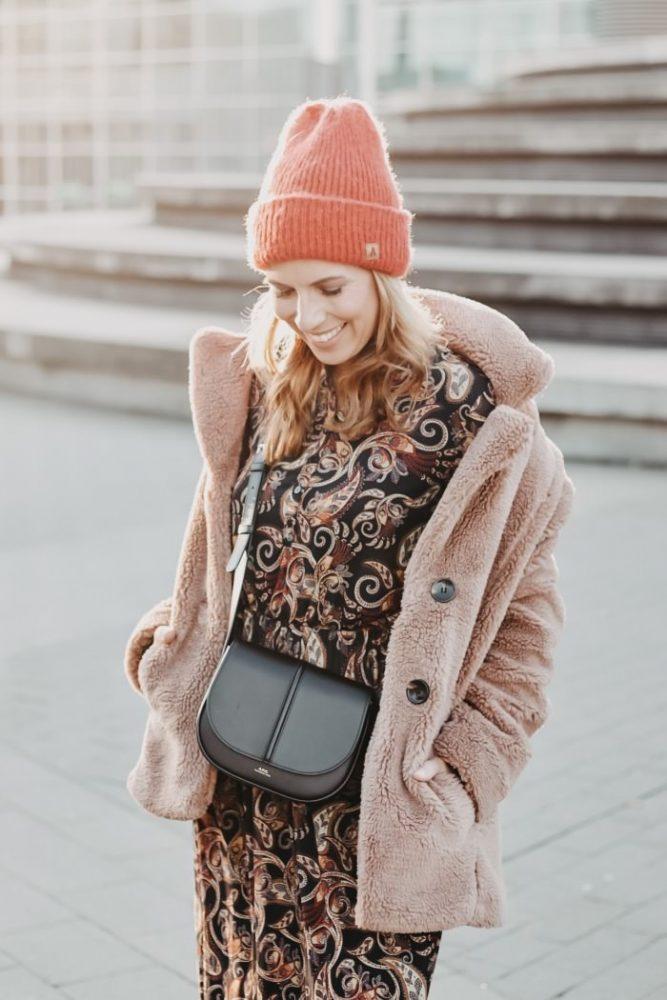 Paisley Kleid kombiniert zu Teddyfleece Jacke, roter Wollmütze und A.P.C. Paris Crossbody Bag