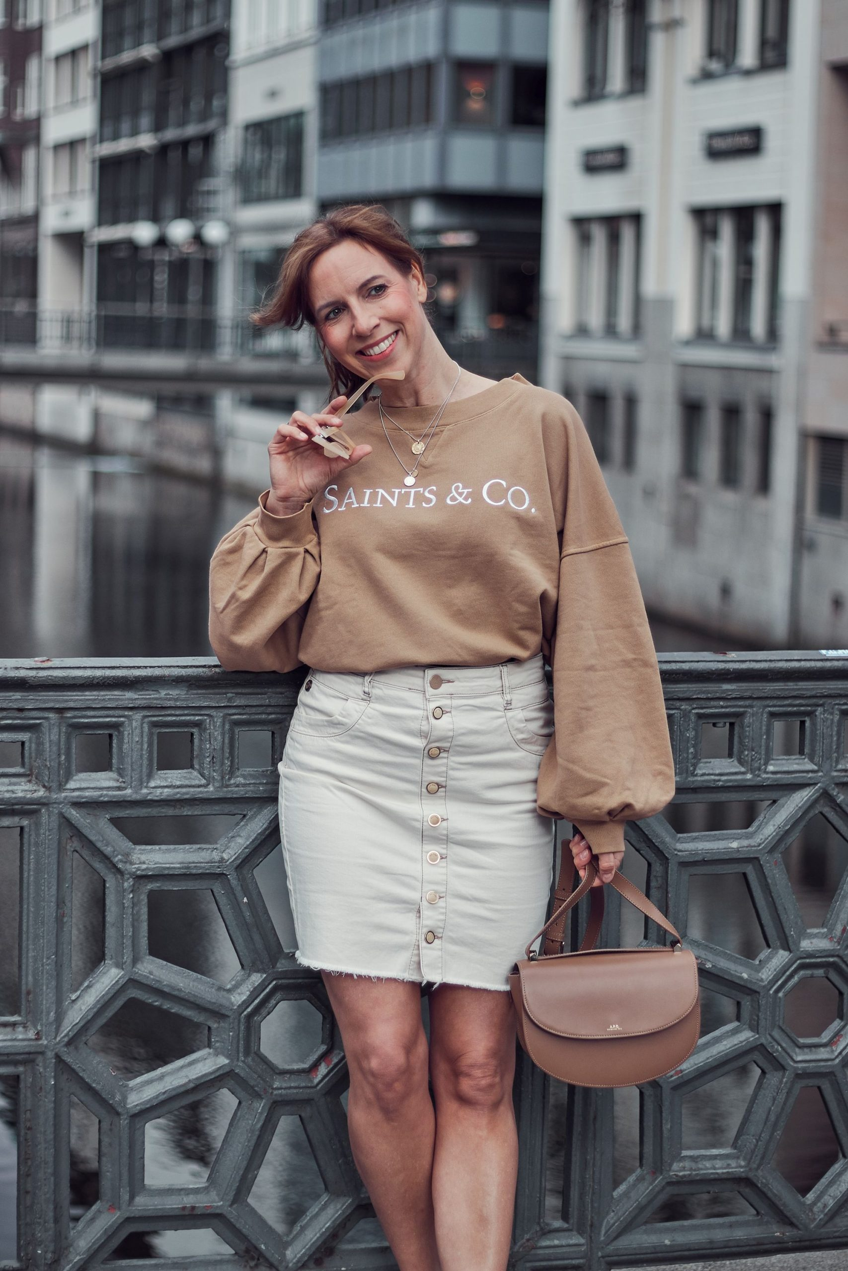 Saints and Co grace Sweater zu cremefarbenem Denim Skirt mit Knopfleiste und Sneakern in weiß.