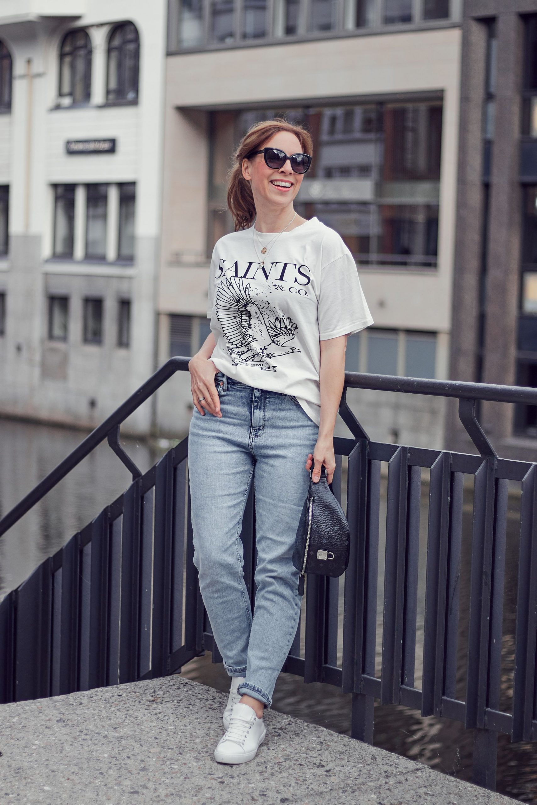 Saints and Co Off-White T-Shirt zu Mom Jeans mit Gürteltasche und Sneakern in weiß.