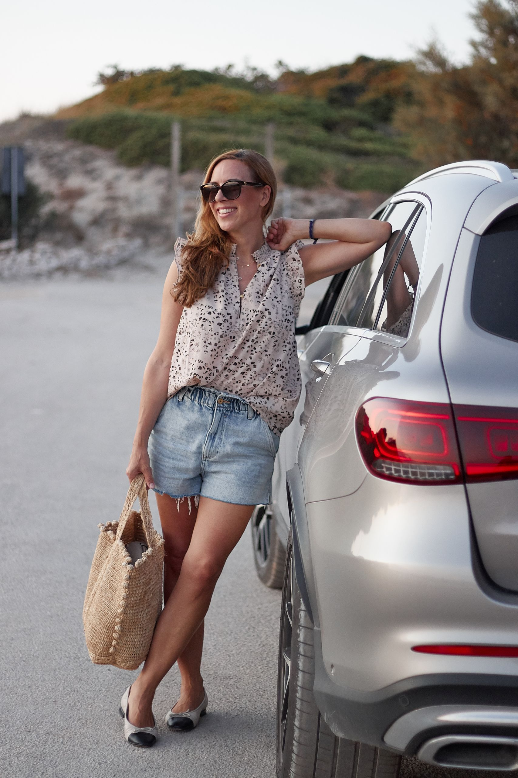 Frau vor dem Auto vor langer Autofahrt mit Baby