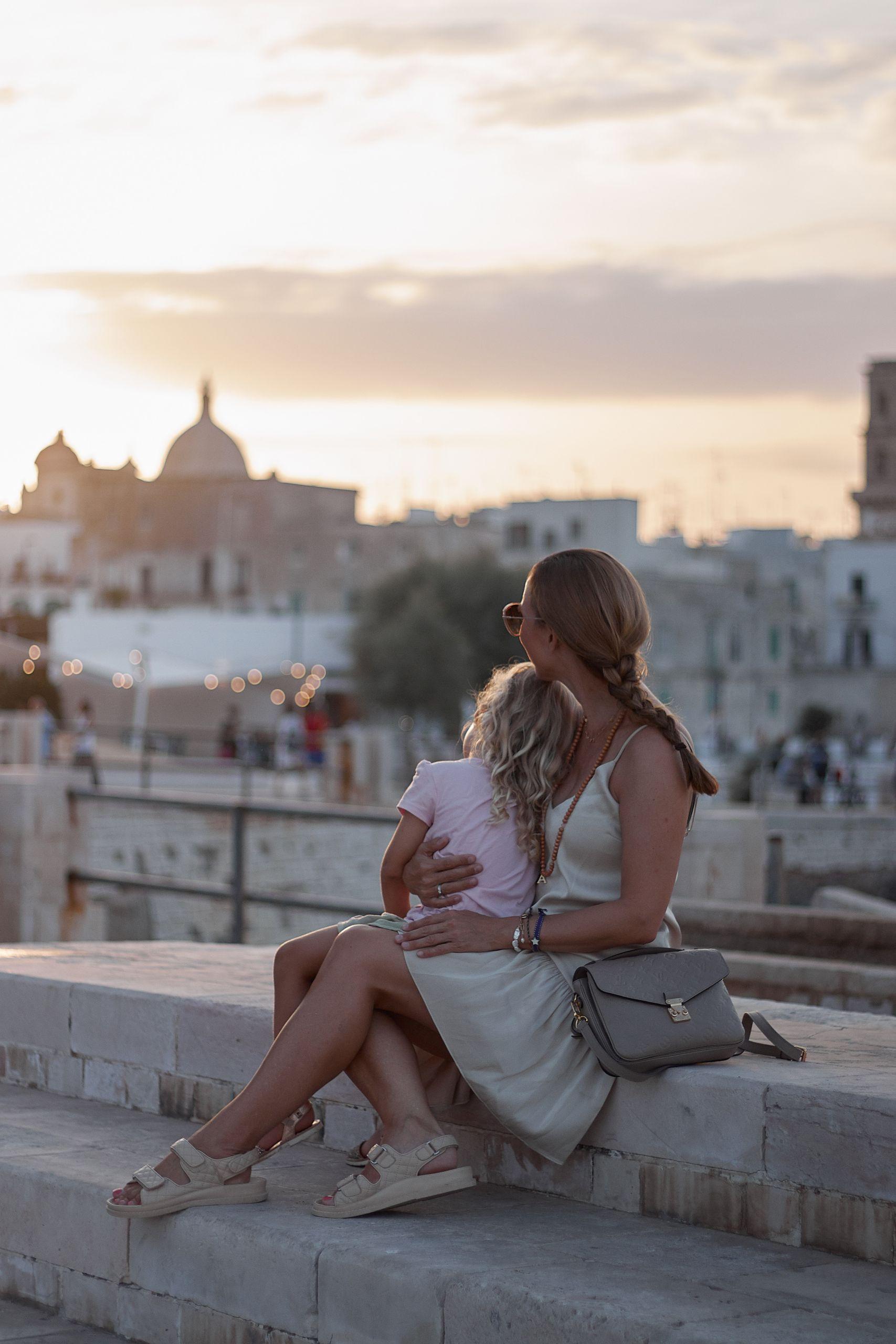 Frau mit Mädchen nach langer Autofahrt mit Baby und Kleinkind in Monopoli